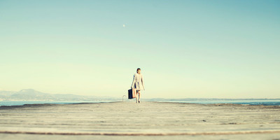 Woman walking down boardwalk alone