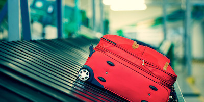 Red Luggage on Conveyor Belt