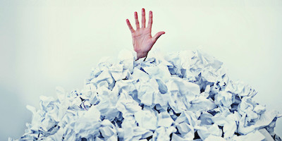 Hand Sticking Out of Pile of Paperwork
