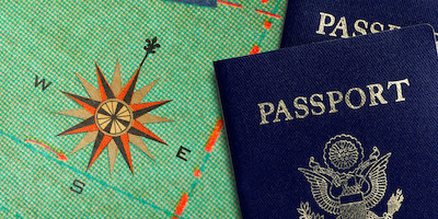 Two Passports Laying Next to the Compass on a Map