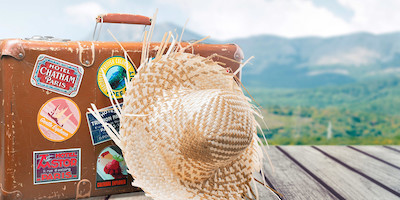 Baggage with Destination Stickers and Straw Hat on Boardwalk
