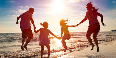 Young Family Jumping in Water at Beach at Sunset