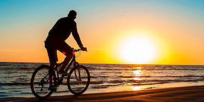 Older Man Biking on Beach at Sunset