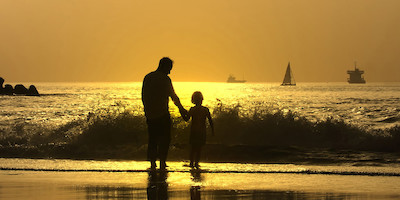 Older Man and Child at Beach at Sunset
