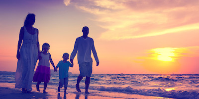Young Family Walking on Beach at Sunset