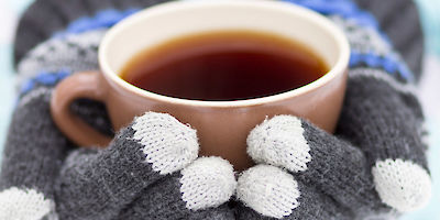 Mug of Coffee in Gloved Hands