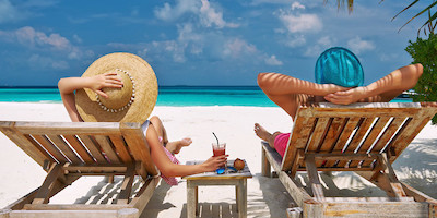 Couple Sitting on Lawn Chairs Looking at Caribbean Sea